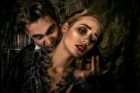 gothic girl: Bloodthirsty male vampire in medieval dress is biting a beautiful lady. Halloween.