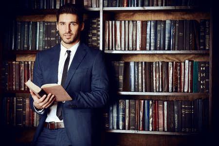 Slušný mladý muž ve staré knihovně. Klasický vintage inter. Reklamní fotografie