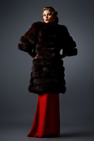 fur coat: Full length portrait of a beautiful woman in red dress and luxurious fur coat. Luxury, rich lifestyle. Fashion shot.