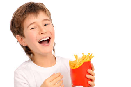 nine year old: Happy nine year old boy eating french fries and laughing. Fast food. Concept of healthy and unhealthy food. Isolated over white.
