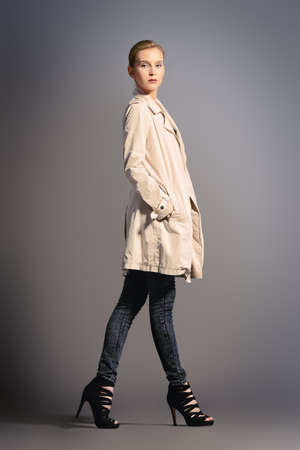 fashionable woman: Fashion shot of a female model posing at studio in a coat