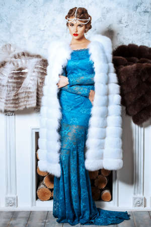 winter fashion: Full length portrait of a stunning young woman wearing evening dress and beautiful furs.