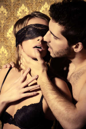 erotic couple: Sensual young woman with lace ribbon on her eyes and a handsome man kissing and playing in love games.