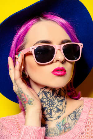 Pretty girl with crimson hair wearing bright clothes and sunglasses posing over yellow background.
