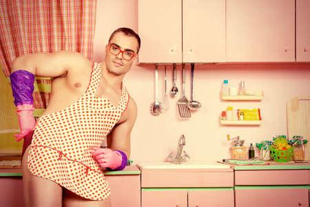 visage homme: Handsome homme musclé dans un tablier de cuisine dans la cuisine rose. Love concept. Saint Valentin.
