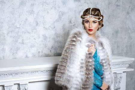 bata blanca: Mujer joven imponente con vestido de noche y hermosas pieles. De lujo, rico estilo de vida. Joyería. Captura de moda. Interior en estilo clásico.