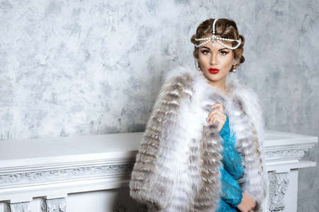 white fur: Stunning young woman wearing evening dress and beautiful furs. Luxury, rich lifestyle. Jewellery. Fashion shot. Interior in classical style.