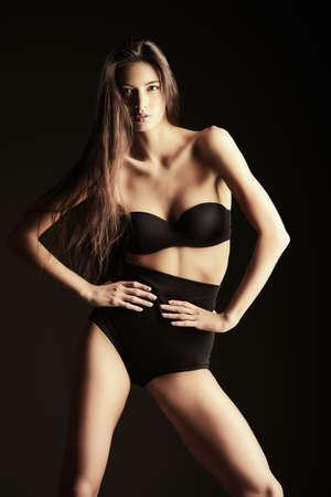 seductress: Beautiful slender woman alluring in black sexy lingerie. Fashion studio shot. Stock Photo