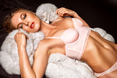 sensual girl: Sexual young woman in a beautiful pink lingerie lying on a white fur over black background.