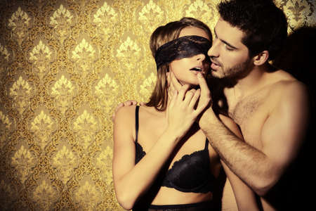 sexo pareja joven: Sensual mujer joven con cinta de encaje en los ojos y un hombre guapo besos y jugar en juegos de amor.