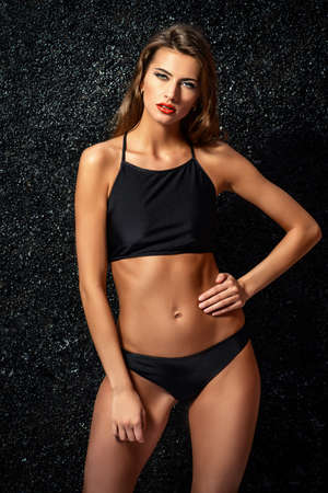 Attractive young woman in black bikini and with bright make-up and beautiful wavy hair. Beauty, fashion. Cosmetics, make-up. Underwear and bikini fashion. Stock Photo