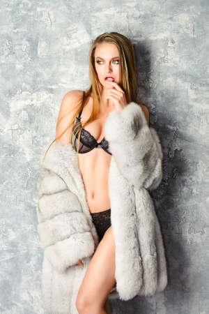 sensual girl: Gorgeous blonde woman posing in luxurious fur coat and lace lingerie. Fashion, beauty. Studio shot.