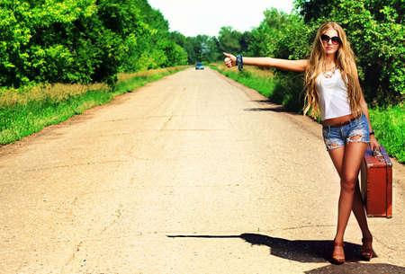 mujer con maleta: Bastante joven haciendo autostop a lo largo de una carretera.
