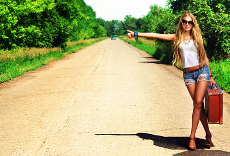 woman freedom: Pretty young woman hitchhiking along a road.