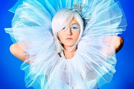 bow hair: Retrato de un modelo extravagante rubia sobre fondo azul.