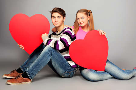 portrait young girl studio: Happy young love couple posing together with red hearts.  Stock Photo