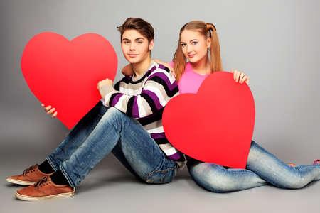 fashionable couple: Pareja feliz amor joven posando juntos con corazones rojos. Foto de archivo