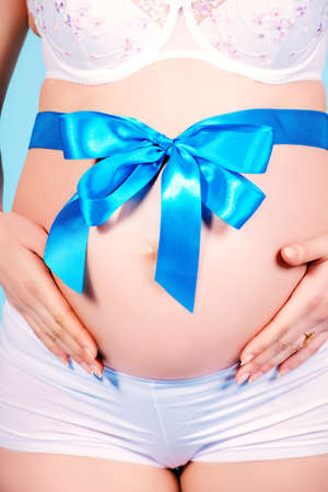bow belly: Close-up shot of a pregnant woman belly with big bow. Pregnancy. Healthcare. Studio shot.