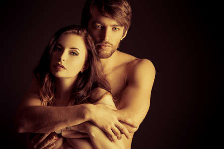 sex tenderness: Beautiful passionate naked couple in love. Over black background.