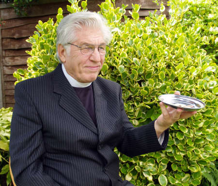 confessor: Vicar passing the plate for the collection