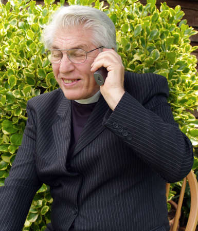 vicar: Vicar speaking on the telephone in the garden