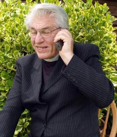 vicar: Vicar speaking on the telephone in the garden