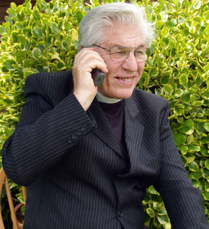 vicar: Vicar on the telephone in the garden        Stock Photo