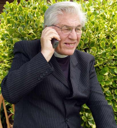 vicar: Vicar on the telephone in the garden        Stock Photo