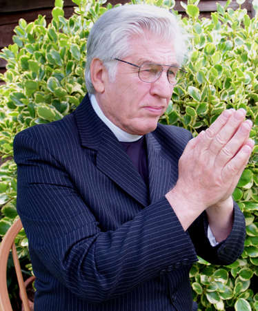 vicar: Vicar praying in the garden in the spring