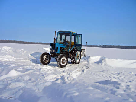Tractor removing snow from the road in the winter photo