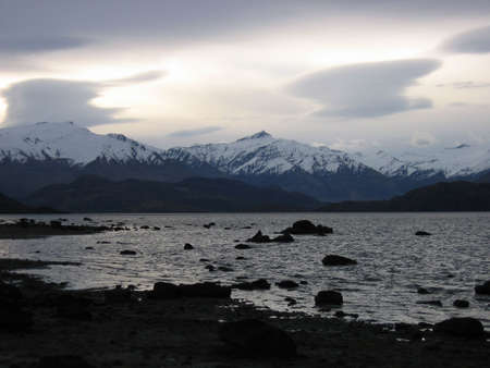 Wanaka lake in the grey day with snow peaks photo