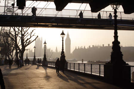 steel bridge: London quay in the fogy day against the sun (London Eye, Parliament, people and lantern silhouettes)