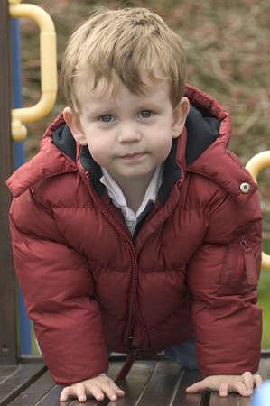 climbing frame: Un ragazzo che indossa un mantello caldo su un giardino di arrampicata telaio.