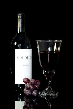 vin: Wine still life, Bottle of Vin de Pays (Country Wine),Glass and red grapes. Black background.
