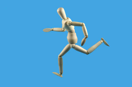 achievment: Wooden mannequin in a running pose, isolated against a sky blue background