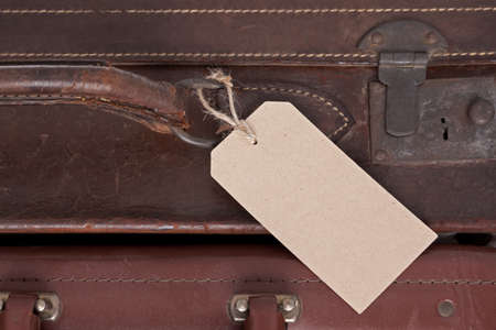luggage tag: Photo of a blank baggage label on an old brown leather suitcase
