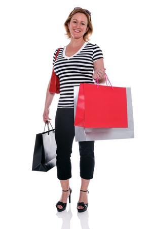 smartly: A smartly dressed mature woman holding shopping bags, isolated on a white background  Stock Photo
