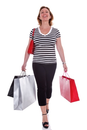 early 40s: A smartly dressed woman in her early 40s carrying shopping bags, isolated on a white background