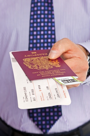 Close-up of a businessman handing over his boarding pass and passport at airport check-in  The tickets are mock ups and all details and names are generic  photo