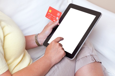 A woman sat at home making an online purchase on her tablet computer about to input her credit card details, screen is blank with a clipping path to add your own details  The card is a mock up made by myself with fake details  photo