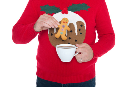 christmas pudding: Man wearing a Christmas jumper about to dip a gingerbread man in a cup of hot chocolate, isolated against a white background.