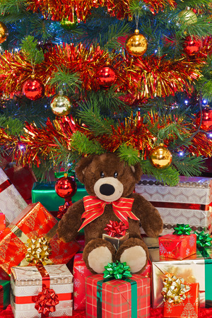 A handmade teddy bear wearing a bow in amongst gifts under a Christmas tree. photo