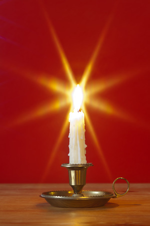 lit candle: A dripping wax candle in a traditional brass holder known as a chamberstick, burning against a red background.  Stock Photo