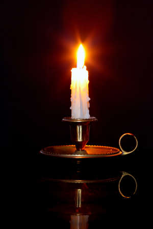 lit candle: A single burning candle in a brass holder known as a chamberstick, against a black background.