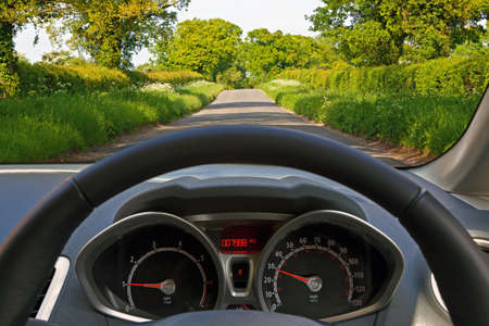 windscreen: View from behind the steering wheel of a car whilst driving down a country road.