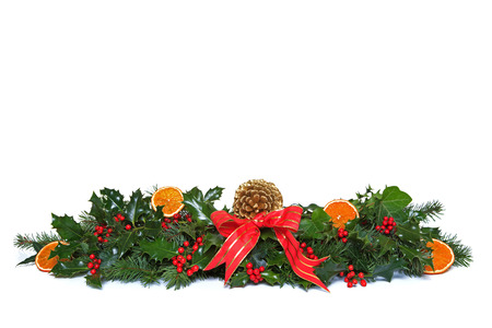 sprigs: A traditional Christmas garland made from fresh holly with red berries, dried orange segments, green ivy, fresh conifer sprigs and pine cone, finished off with a red ribbon and bow. Isolated on a white background. Stock Photo