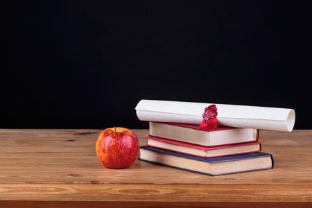 licenciatura: Escuela de escritorio con libros y un diploma sobre un fondo negro, añada para poseer el texto.