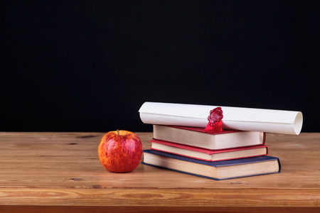 schooltime: School desk with books and a diploma against a black background, add you own text. Stock Photo