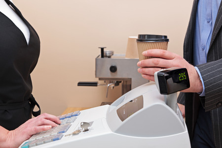 till: Man standing by the till in a coffee shop buying a takeaway drink in a paper cup. Stock Photo