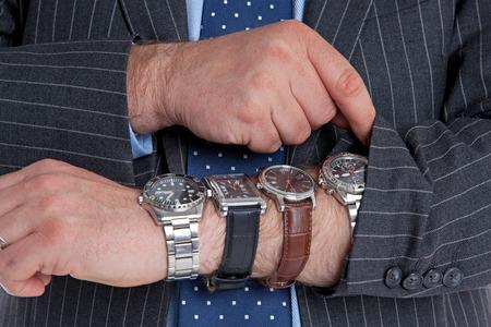 cronógrafo: Hombre de negocios con cuatro relojes de pulsera comprobando el tiempo. Buena imagen para temas relacionados con el tiempo. Foto de archivo